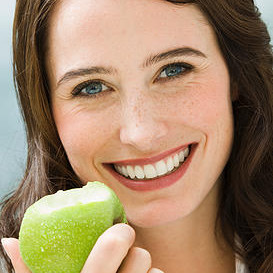 Woman eating apple, smiling, close-up